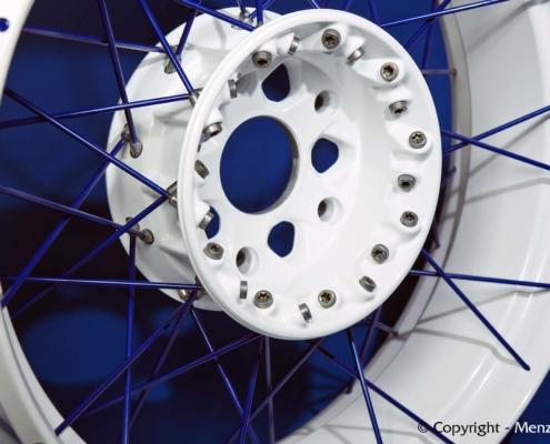 Kreuzspeichenfelge in weiß mit Speichen in blau pulverbeschichten